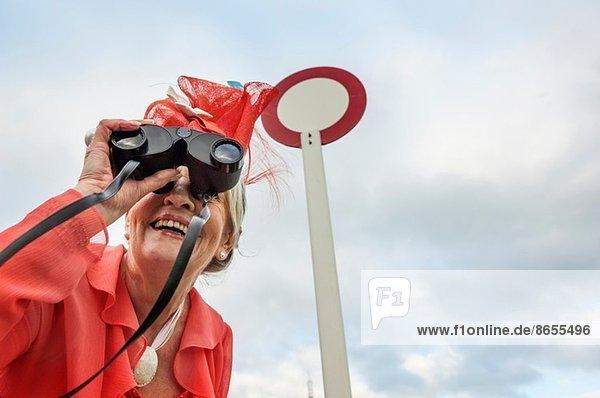 Seniorin bei Rennen  die sich nach vorne lehnt und durchs Fernglas schaut.
