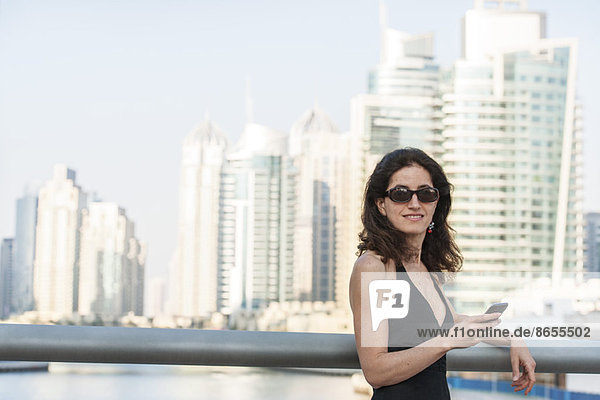 Frau lehnt an Geländer mit Smartphone in der Hand  Wolkenkratzer im Hintergrund