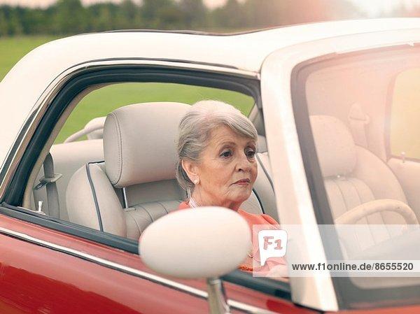 Seniorin fährt rotes Cabriolet