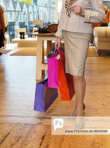 Glamouröse Seniorin mit Einkaufstaschen in der Boutique