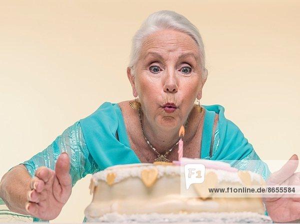 Studio-Porträt der Seniorin beim Ausblasen der Geburtstagskerze