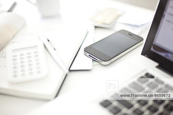 Smartphone im Home-Office auf dem Schreibtisch liegend