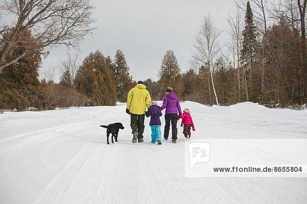 Mutter und Vater mit zwei Kindern und Hund  Spaziergang im Schnee  Rückansicht