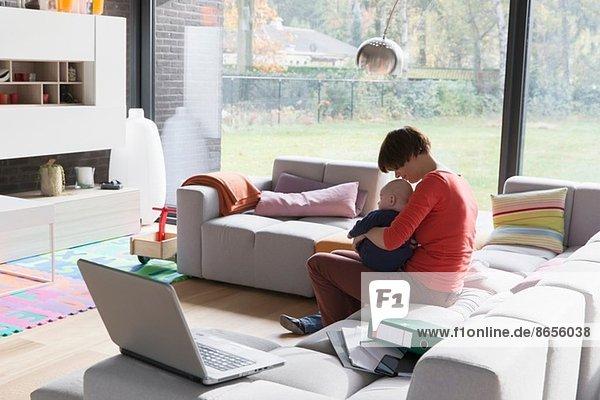 Mutter mit Kind auf dem Sofa zu Hause sitzend
