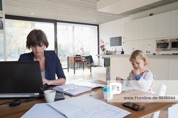 Mutter mit Kleinkind bei der Arbeit am Computer am Küchentisch