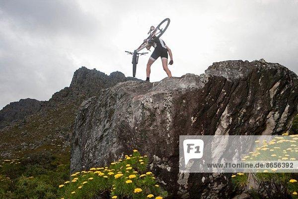 Junger Mann mit Mountainbike auf dem Gipfel der Felsformation