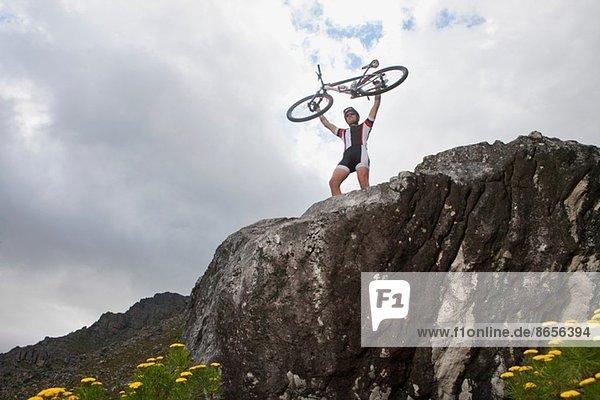 Junger Mann hält Mountainbike auf dem Felsen hoch