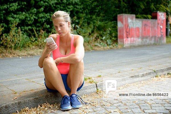 Junge Läuferin auf dem Bürgersteig sitzend mit dem Handy