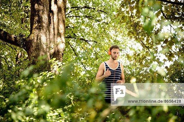 Junger Mann in Kopfhörern  der im Wald läuft.