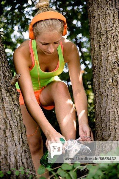 Junge Läuferin beim Schnürsenkelbinden im Wald