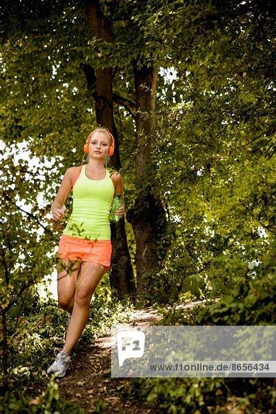 Junge Frau im Kopfhörer im Wald unterwegs