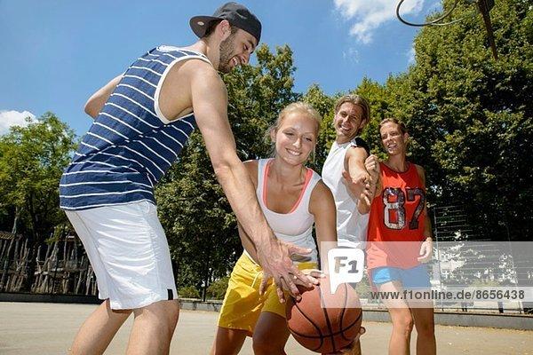 Gruppe von Freunden beim Basketball im Park