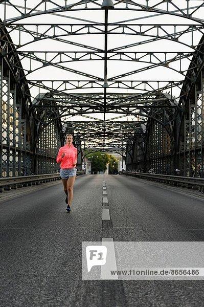 Junge Läuferin über die Brücke