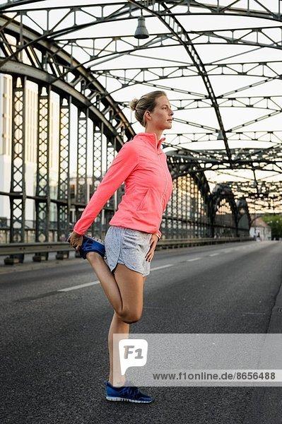 Junge Läuferin beim Strecken auf der Brücke
