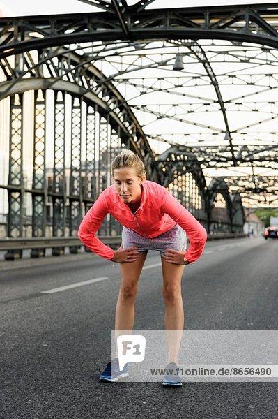 Junge Läuferin beim Laufen auf der Brücke