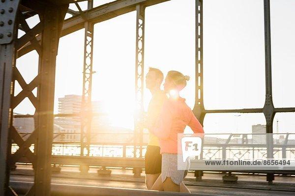 Junges Männchen und Weibchen auf der Brücke laufend