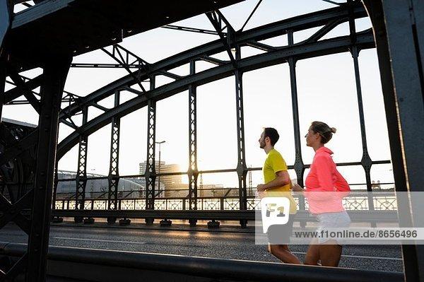 Junge Läuferinnen und Läufer über die Brücke