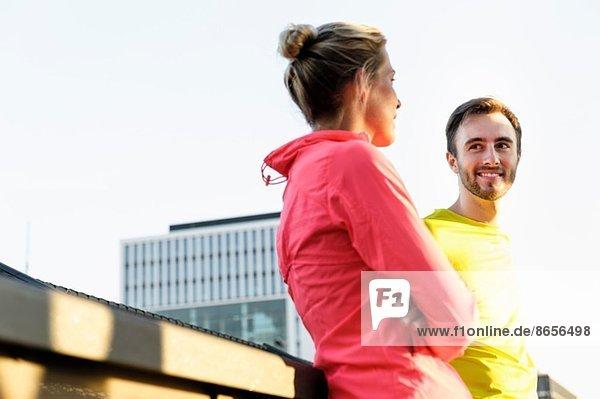 Junge Läuferinnen und Läufer im Gespräch auf der Brücke
