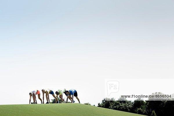 Gruppe erwachsener Läufer  die sich auf den Lauf vorbereiten.