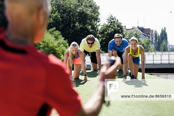 Erwachsener Mann  der eine Gruppe erwachsener Läufer am Start trainiert.