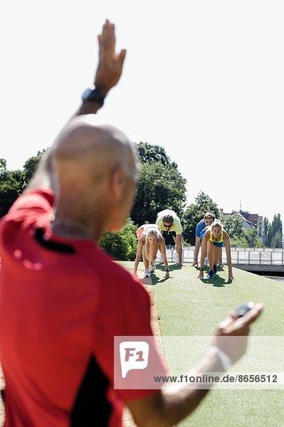 Erwachsener Mann  der eine Gruppe erwachsener Läufer an der Startlinie vorbereitet.