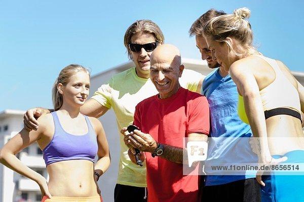Reife männliche Trainerin und eine Gruppe erwachsener Läuferinnen und Läufer