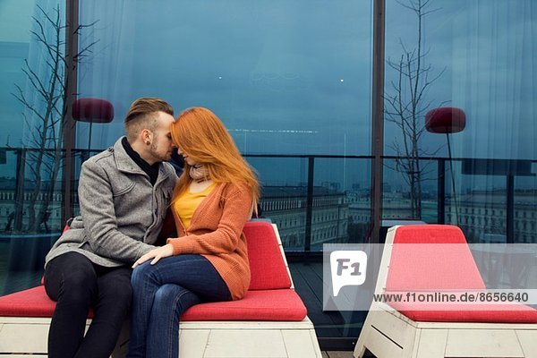 Romantic young couple sitting outdoors on rooftop terrace