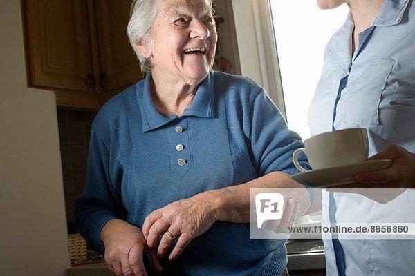 Körperpflege-Assistentin mit einer Tasse Tee für Seniorinnen