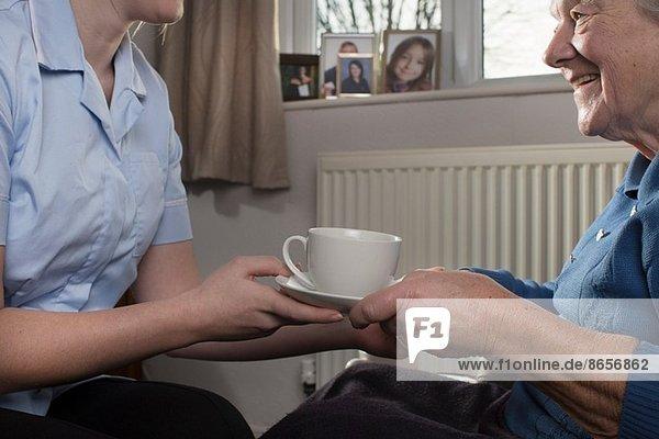 Körperpflege-Assistentin bei der Übergabe einer Tasse Tee für Seniorinnen