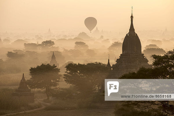 Hot air balloon over the landscape in the early morning fog  temples  stupas  pagodas  temple complex  Plateau of Bagan  Mandalay Division  Burma or Myanmar