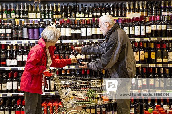 Seniorenpaar beim Einkaufen in der Weinabteilung im Supermarkt  Deutschland