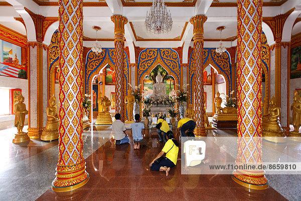 Besucher beten vor Altar im buddhistischen Wat Chalong Tempel  Säulen  Phuket  Thailand