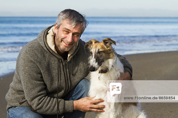 Borzoi or Russian Wolfhound  with a man by the sea  Tuscany  Italy