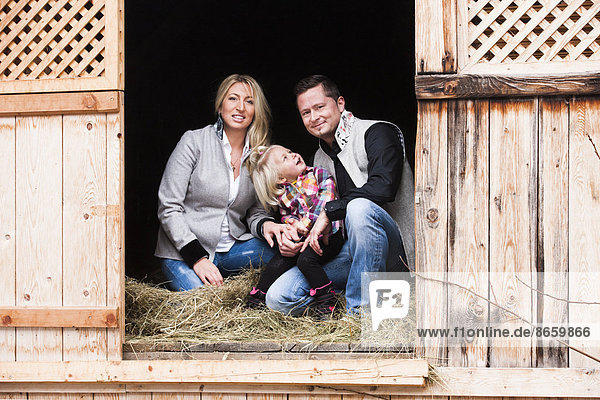 Young family sitting in the hay barn  North Tyrol  Austria