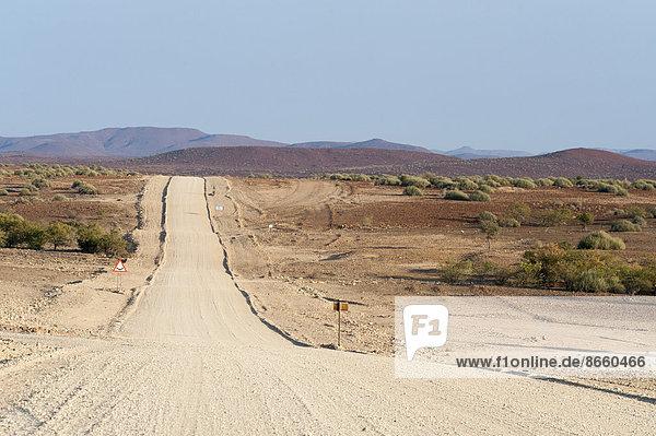 Breite  gerade Schotterstraße in trockener Landschaft  Region Kunene  Namibia