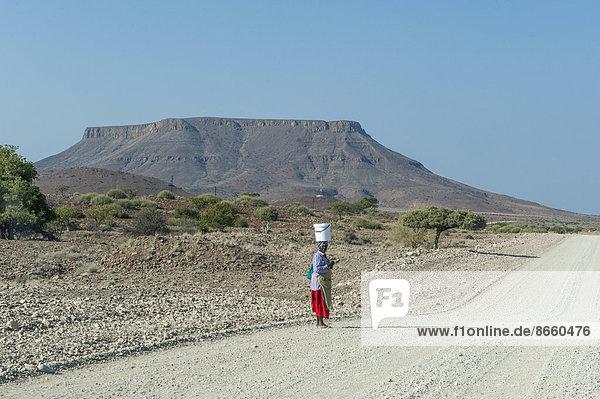 Frau mit einem Eimer auf ihrem Kopf steht an einer Schotterstraße in trockener Landschaft  Region Kunene  Namibia