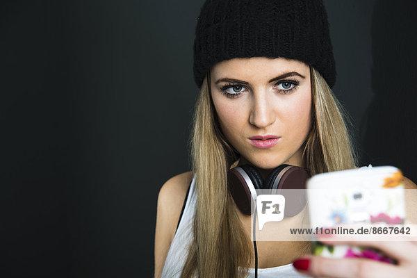 Junge Frau mit Kopfhörer und Mütze