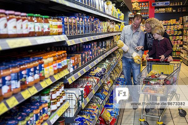 Familie mit Einkaufswagen beim Einkaufen im Supermarkt,  Gang mit verschiedenen Lebensmitteln,  Deutschland
