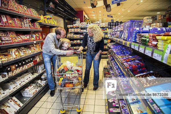 familie beim einkaufen in der s igkeiten abteilung im supermarkt deutschland ibljot03841106. Black Bedroom Furniture Sets. Home Design Ideas