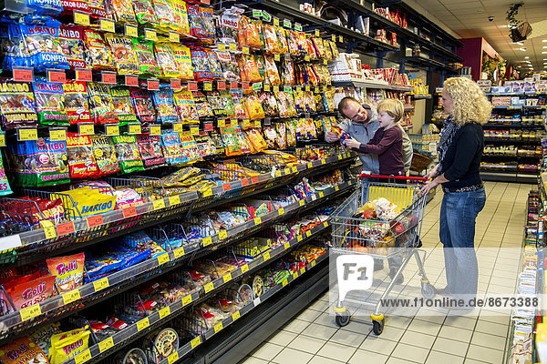 Familie beim Einkaufen in der Süßigkeiten-Abteilung im Supermarkt  Deutschland