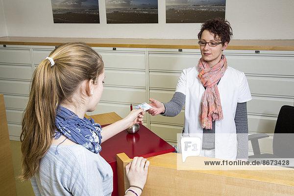 Arztpraxis  Patientin und Sprechstundenhilfe am Empfang  Gesundheitskarte  Deutschland