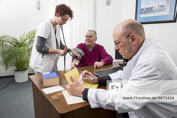 Arztpraxis  älterer Patient bekommt von einer Arzthelferin den Blutdruck gemessen  Deutschland