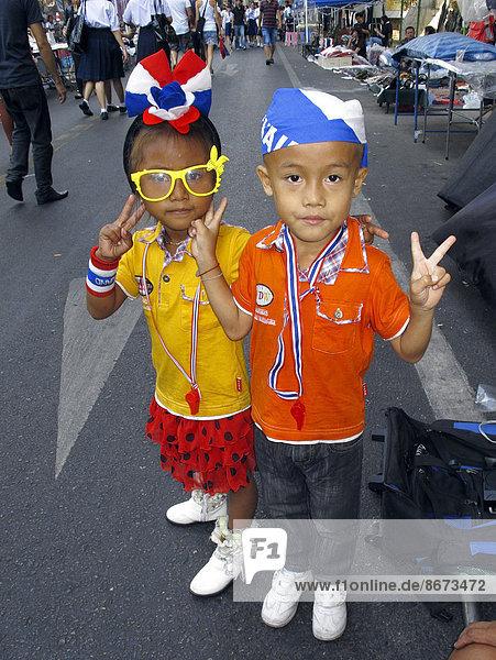 Zwei verkleidete Kinder machen das V-Zeichen bei einer Antiregierungsdemonstration  Bangkok  Thailand Zwei verkleidete Kinder machen das V-Zeichen bei einer Antiregierungsdemonstration, Bangkok, Thailand