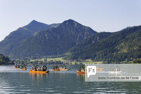 Trachtler in festlich geschmückten Plätten  Holzbooten  hinten der Brecherspitz  Alt-Schlierseer-Kirchtag  Schliersee  Oberbayern  Bayern  Deutschland