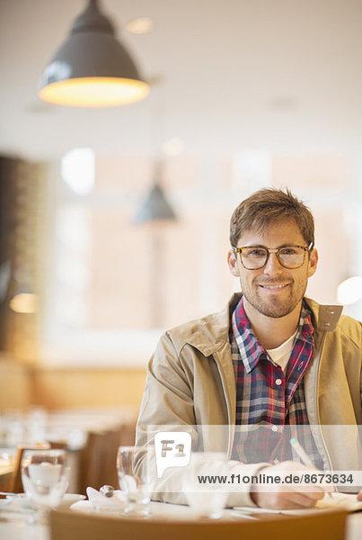 Mann macht Notizen im Café