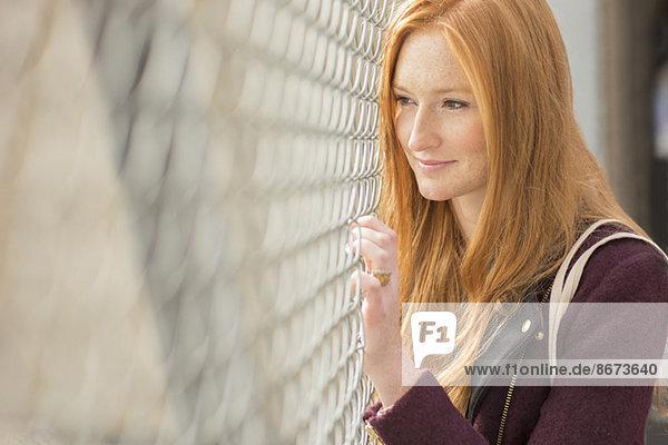 Frau blickt durch den Kettengliederzaun