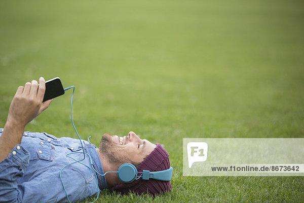 Mann hört Kopfhörer auf dem Rasen