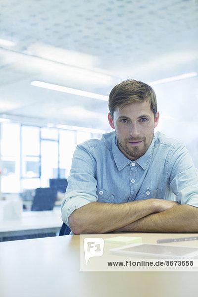 Geschäftsmann am Schreibtisch im Büro sitzend