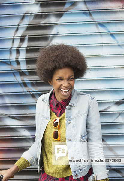 Frau lacht vor der Graffiti-Wand