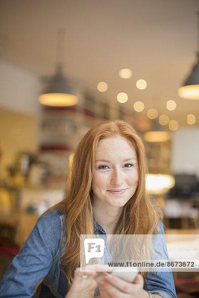 Frau benutzt Handy im Cafe